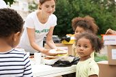 Volunteer sharing food with poor African children outdoors poster