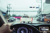 Driving in rainy day, Hand holding steering wheel with car traffic in the city in raining day