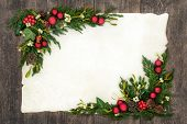 Christmas background  border on parchment paper on oak wood with red bauble decorations, holly, mist poster