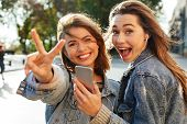 Two happy teen girl showing peace sign while listening to music on smartphone, looking at camera, ou poster