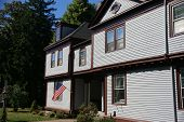 American Flag And Classic New England House