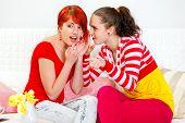 Girl whispering gossips in ear of her interested girlfriend and pointing finger in corner