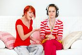 Sitting on sofa indignant young girl pointing on her girlfriend listening something in headphones