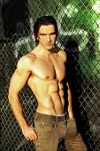 Sexy male fashion model shirtless against graffiti and fence