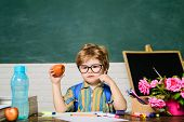 Pupil From Elementary School In Classroom. Little Pupil Having Lunch With Apple In Classroom. Elemen poster