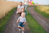 Happy Family Enjoy Weekend In Nature. Loving Parents Watch Their Son Doing First Steps. Baby Learnin poster