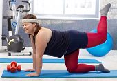 Young fat woman doing gymnastics at the gym, smiling.
