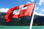 Switzerland flag with lake and mountain in the background