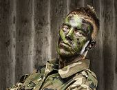 portrait of a young soldier with a jungle camouflage paint against a grunge background