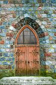 Old Wooden Door In Old Town, Europe. Old Wooden Door In The Entrance Stone Europe House poster