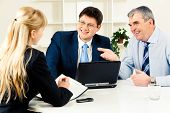 picture of business-partner  - Three business partners discussing new working ideas around table with laptop on it - JPG