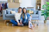 Young beautiful couple sitting on the floor of new apartment, smiling in love happy for moving to a  poster