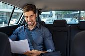 Business man looking at documents in his car. Young happy businessman reading contract on car back s poster