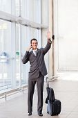 stock photo of bye  - young businessman waving good bye at airport - JPG