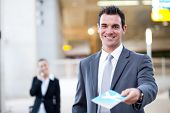 picture of over counter  - businessman handing over air ticket in airport check in counter - JPG