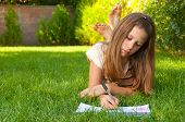 Cute teenage girl lies on the grass and draws in her notebook on sunny summer day