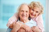 image of flirty  - Happy elderly couple hugging in front of the camera - JPG