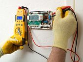 stock photo of voltage  - Male hispanic air conditioning and heating technician repairman - JPG