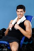 Athletic man rests sitting on blue simulator in training gym