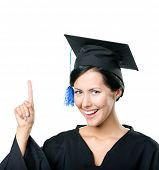 stock photo of school-leaver  - Graduating student in black academic gown and cap making the attention gesture - JPG