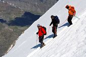 Team of alpinists descending an icy slope