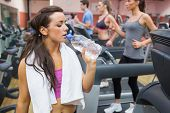 Woman drinking bottle of water in the gym during exercise beside treadmill