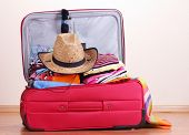 stock photo of carry-on luggage  - Open red suitcase with clothing in the room - JPG