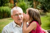 stock photo of grandfather  - Little girl whispering her grandfather a secret to ear  - JPG