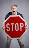 Serious man shouting while showing stop sign isolated on grey background.