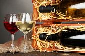 Wooden case with wine bottles and wineglasses on grey background