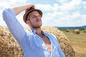 young casual man leaning back on a haystack while holding his hat and a straw behind his ear and his