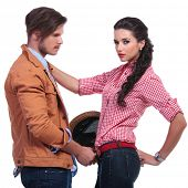 young casual couple with man taking woman's belt off while she is looking into the camera. on white background