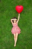 Beautiful Girl Lying On The Grass And Holding A Red Ball In The Form Of Heart