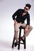 full length portrait of a young fashion man sitting on a chair and looking at his side, away from th