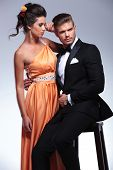 young fashion couple with seated man holding standing woman while looking away from the camera. on g