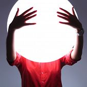 young casual woman covering her eyes over a shiny blank circle. see no evil concept. on gray background