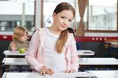 Portrait of cute little girl studying while standing at desk with classmates in background
