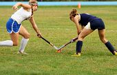 picture of battle  - Two women battle for control of ball during field hockey game - JPG