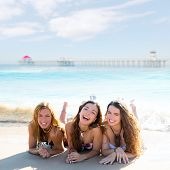 happy three teen friends girls lying on beach sand smiling at Huntington Beach California [photo-ill