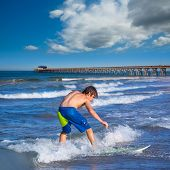 Boy surfer surfing waves on Newport pier beach  California [photo-illustration]