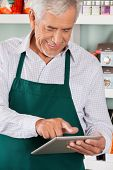 image of self-employment  - Happy senior male owner using digital tablet in grocery store - JPG