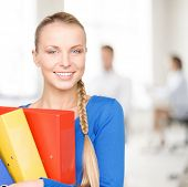 office, buisness, teamwork concept - young attractive businesswoman with folders