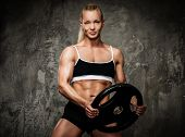 stock photo of barbell  - Beautiful muscular bodybuilder woman with weights - JPG