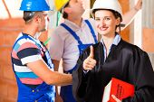 Reviewer or expert or lawyer and builder or worker with helmets controlling a construction or buildi