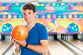 Young man in bowling alley having fun, the sporty man holding a bowling ball in front of the ten pin