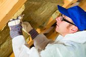stock photo of modification  - Worker in overall is setting thermal insulating material with gloves in the roof - JPG