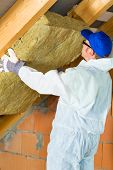 stock photo of overalls  - Worker in overall is setting thermal insulating material with gloves in the roof - JPG