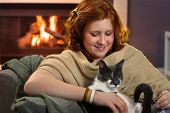 Happy teenage girl sitting at fireplace at home caressing cat.