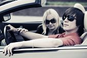 Young couple driving a convertible car