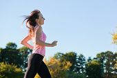 Young fit woman does running, jogging training in a park at summer sunny day. Profile view